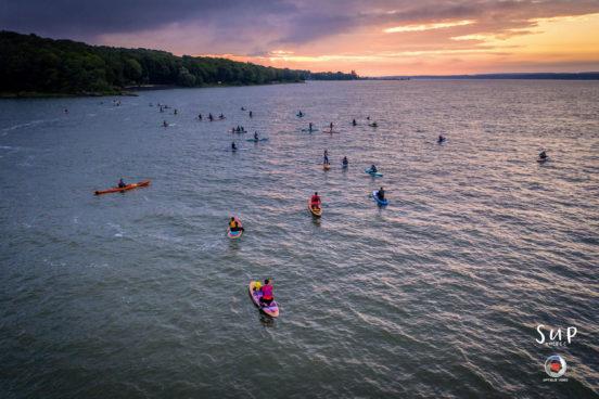 A large group at sunrise paddleboarding.