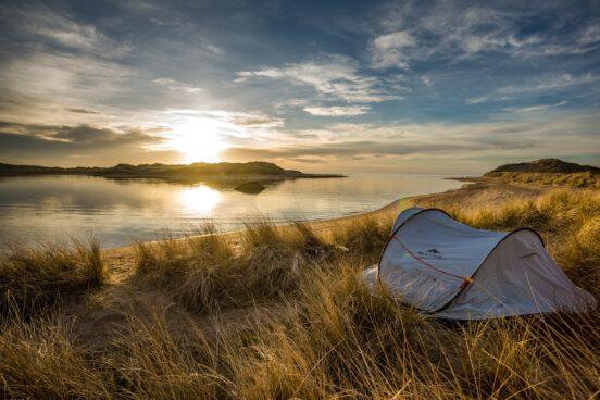 A photo of a tent a sunrise.