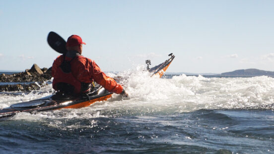 A kayaker paddling out in surf in a sea kayak.