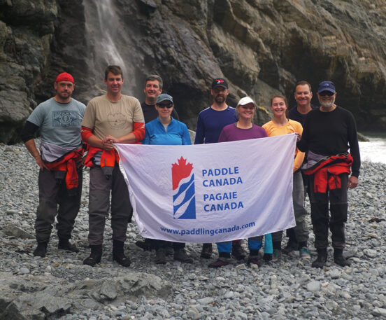 A group of paddlers who recently took a Paddle Canada course with the Paddle Canada flag in front of them.