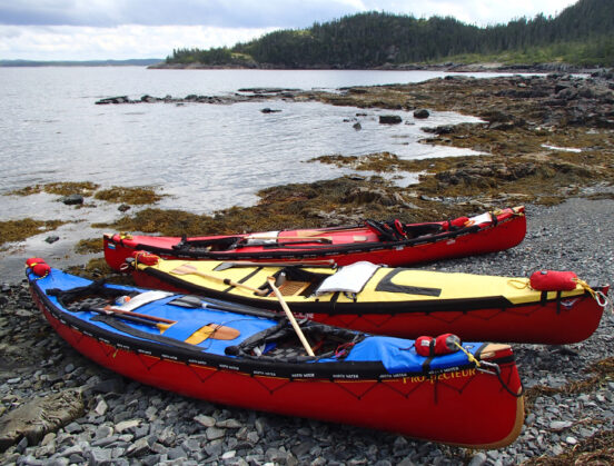 Three canoes pulled up on shore along an ocean coastline.