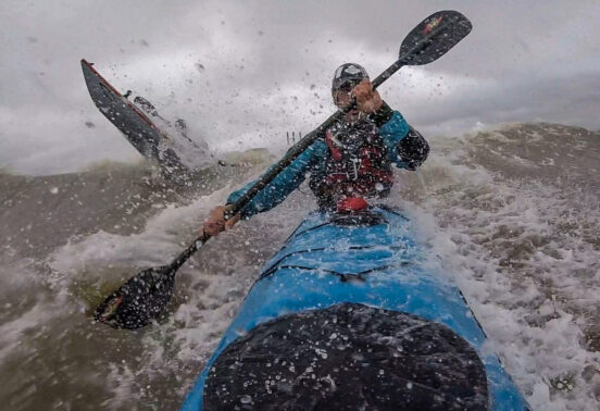 Adam Constantine and Peter Lavigne breaking out in surf in their kayaks in Bay of Fundy, Saint John NB.