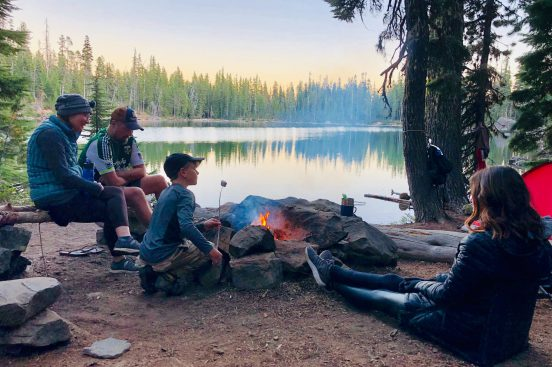 A family cooking marshmallows over a fire while camping by a lake and learning how to camp.