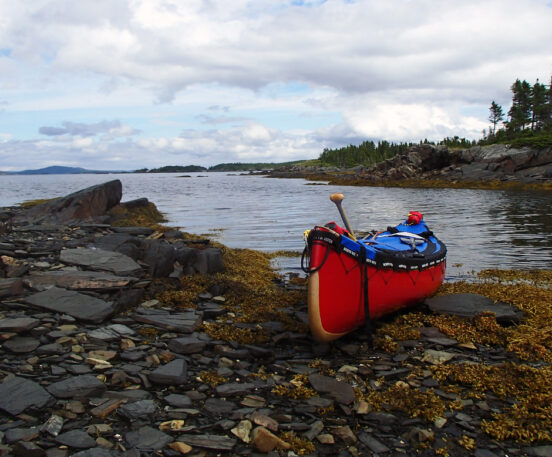 A canoe with a blue spray skirt on top pulled up on shore with the ocean and rocks.