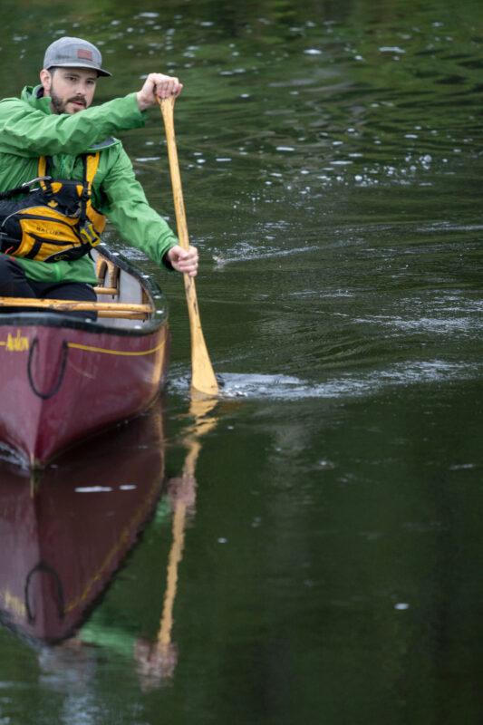 Gentleman paddling a canoe solo.
