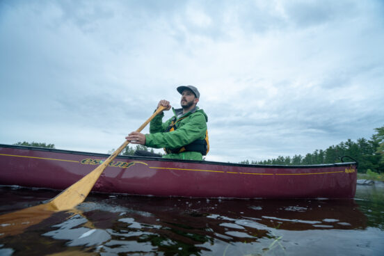Man solo canoeing on calm water.