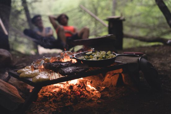 Two people camping and cooking over a fire.