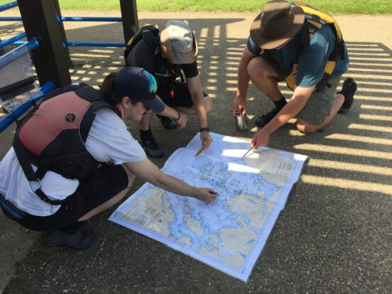 People staring at a nautical chart during a navigation lesson.