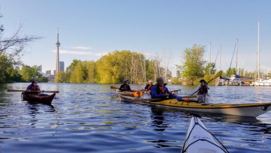 A group of friends kayaking in the Toronto Islands.