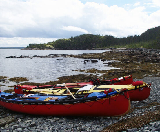 Two canoes pulled up on shore along a rocky ocean coastline.