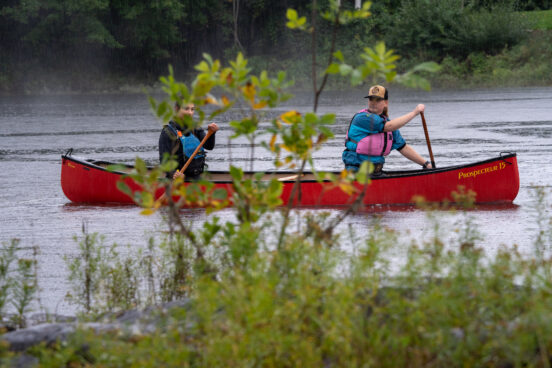 Two ladies in a canoe paddling in the rain.