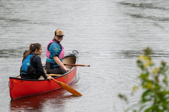 Two ladies canoeing in the rain.