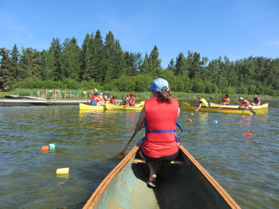 Kids paddling a canoe as part of a waterfront canoe course.