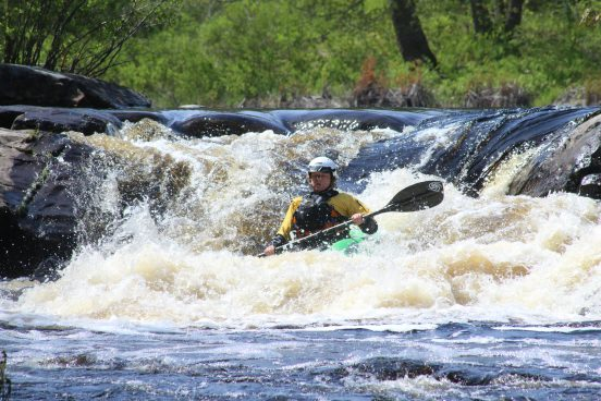 A lady in a whitewater kayak going over a waterfall in Nova Scotia.