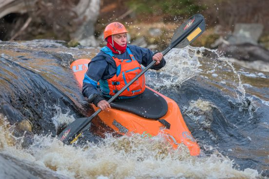 A older gentlemen paddles into a hole in a whitewater kayak.