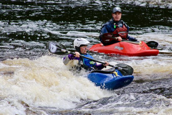 A whitewater instructor keeps and eye on a lady learning how to surf in a whitewater kayak.