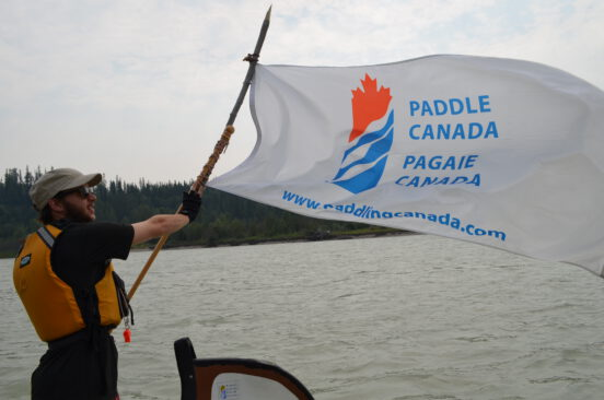 A man holding the Paddle Canada flag.