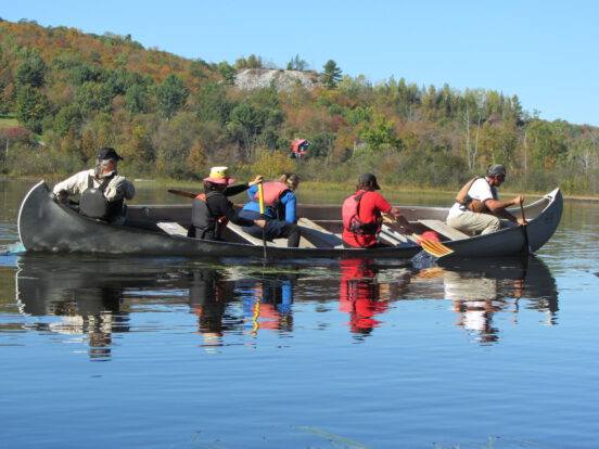 People in a big canoe on the Gatineau River, Quebec.