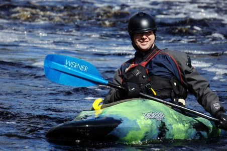 A guy in a kayak is happy after paddling down a section of whitewater in Nova Scotia.