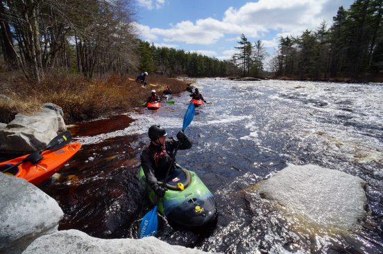 A group of kayakers wait below a bridge embankment to go whitewater kayaking.