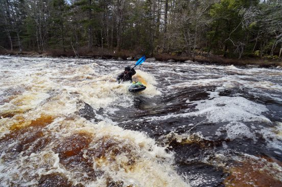 A man in a whitewater kayak about to surf in a whitewater hole.