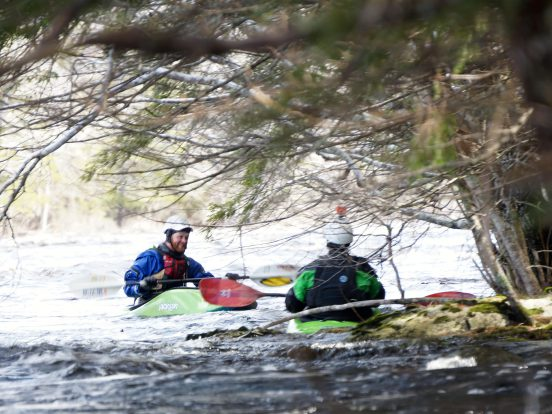 Two guys gather up to talk while in their whitewater kayaks on a river.