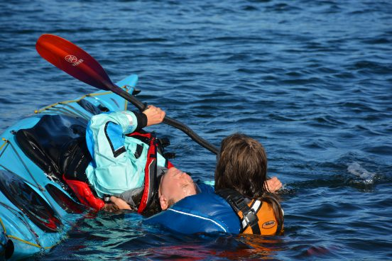 A student learning how to roll her sea kayak.