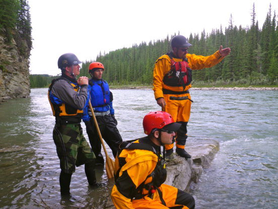 Students learn about how to read whitewater on an intermediate moving water course with Priscilla Haskin on the Red Deer River, AB.