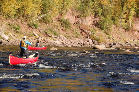 A student learning intermediate canoe poling techniques on the Miramichi River, NB with Tim Humes.
