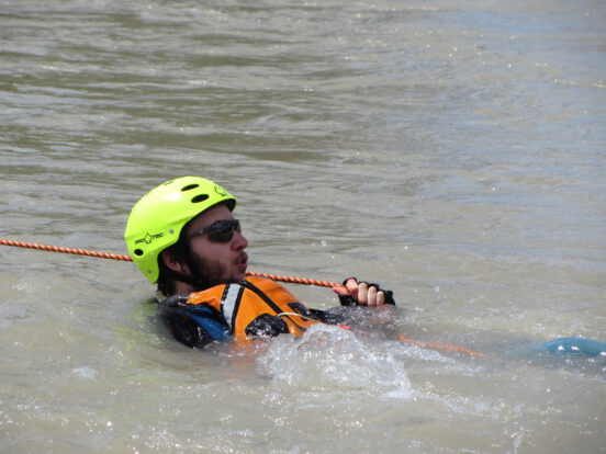 A swimmer in moving water during a river rescue course holding onto a rope.