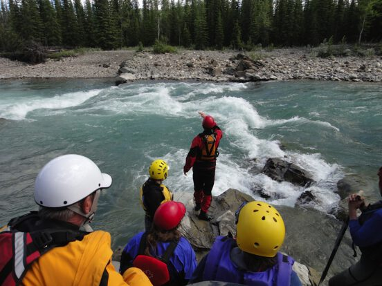 A teaching showing students where to paddle down moving water on the Red River, AB