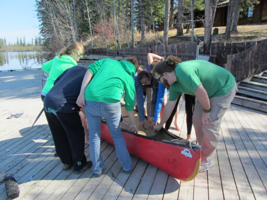Students learning about parts of a canoe during a course on Crimson Lake, AB.