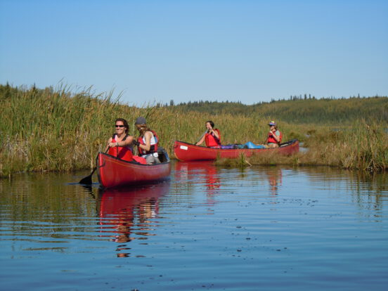 Students canoeing out of a marsh on a canoe course on Jackson Lake, AB