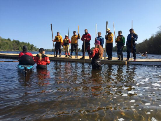 Students on a dock with kayak paddles learning how to teach kayak rolling.