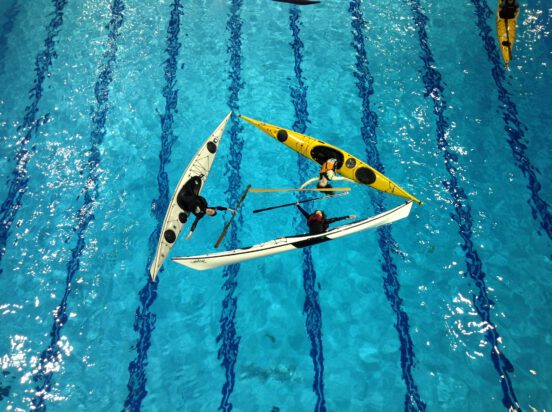 Three ladies in kayaks in a pool doing a paddle brace.